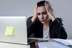 Bedrijfsvrouw die aan laptop op kantoor in spanning werken die aan intense hoofdpijnmigraine lijden Royalty-vrije Stock Foto