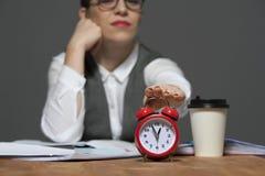 Bedrijfsvrouw die aan lijst met rode wekker zitten royalty-vrije stock fotografie
