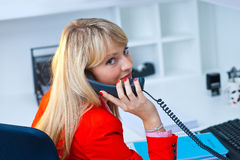 Bedrijfsvrouw die aan telefoon in bureau spreken Royalty-vrije Stock Afbeeldingen