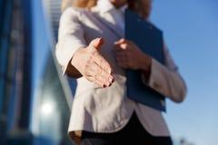 Bedrijfsvrouw die blauwe omslag houden die die wapen geven voor handdruk wordt uitgebreid stock afbeeldingen
