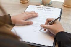 Bedrijfsvrouw die de vorm van het contractdocument ondertekenen Stock Foto's