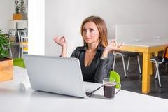 Bedrijfsvrouw die dichtbij laptop mediteren Ontspannen beambte die yogameditatie doen tijdens een koffiepauze Groen eco gezond bu Stock Foto's