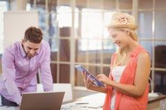 Bedrijfsvrouw die digitale tablet met mannelijke collega gebruiken die aan laptop werken Stock Fotografie