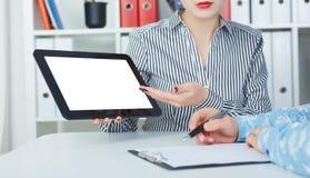 Bedrijfsvrouw die digitale tablet tonen aan medewerkers in bureau Stock Afbeelding
