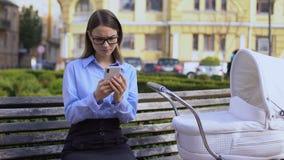 Bedrijfsvrouw die e-mail die op smartphone verzenden baby in vervoer, carrière negeren stock videobeelden