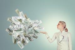 Bedrijfsvrouw die een bos van dollars blazen Royalty-vrije Stock Foto's