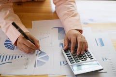 Bedrijfsvrouw die een calculator gebruiken om de aantallen te berekenen Stock Foto