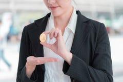 Bedrijfsvrouw die een gouden bitcoin cryptocurrency houden stock fotografie