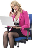 Bedrijfsvrouw die een Laptop Computer en een Mobiele Celtelefoon met behulp van Royalty-vrije Stock Foto