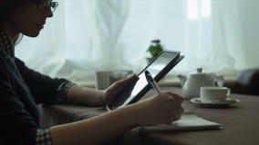 Bedrijfsvrouw die een tablet en een notitieboekje in koffie gebruikt stock videobeelden