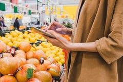 Bedrijfsvrouw die een tablet in een supermarktclose-up houden royalty-vrije stock afbeeldingen