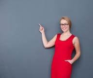 Bedrijfsvrouw die en aan exemplaarruimte glimlacht richt Royalty-vrije Stock Foto's