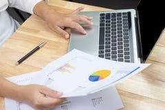 Bedrijfsvrouw die financiële document grafieken houden en met laptop computer werken stock afbeeldingen