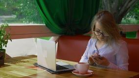Bedrijfsvrouw die glazen dragen die in koffie werken en op slimme telefoon spreken stock video