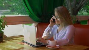 Bedrijfsvrouw die glazen dragen die in koffie werken en op slimme telefoon spreken stock videobeelden