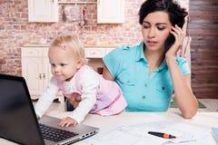 Bedrijfsvrouw die haar babymeisje werken Royalty-vrije Stock Afbeeldingen