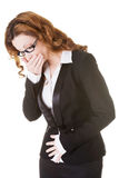 Bedrijfsvrouw die haar maag houden en mond behandelen. royalty-vrije stock fotografie