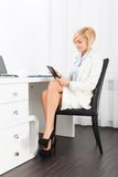 Bedrijfsvrouw die het bureau van de tabletzitting gebruiken Royalty-vrije Stock Foto's