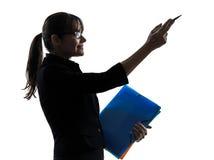 Bedrijfsvrouw die het richten tonen   de holdingsomslagen dient silhouet in Stock Foto's