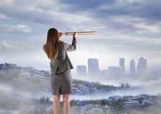 Bedrijfsvrouw die horizon met telescoop van nevelige bergpiek waarnemen Stock Fotografie