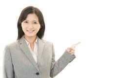 Bedrijfsvrouw die iets op de palm van haar hand tonen Royalty-vrije Stock Fotografie