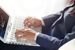 Bedrijfsvrouw die laptop computer op zonlichtachtergrond met behulp van Royalty-vrije Stock Foto's