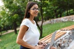 Bedrijfsvrouw die laptop computer in openlucht met behulp van royalty-vrije stock afbeelding