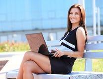 Bedrijfsvrouw die laptop in openlucht met behulp van stock foto