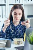 Bedrijfsvrouw die lunch eten op het haar werk die het laptop scherm bekijken Omslagen met documenten in de voorgrond stock afbeeldingen