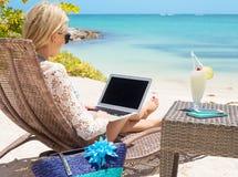 Bedrijfsvrouw die met computer aan het strand werken
