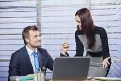 Bedrijfsvrouw die met een man in het bureau flirten stock afbeelding