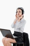 Bedrijfsvrouw die met hoofdtelefoons voor laptop zitten wit Royalty-vrije Stock Afbeelding