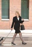 Bedrijfsvrouw die met reisbagage lopen in de stad Stock Foto's