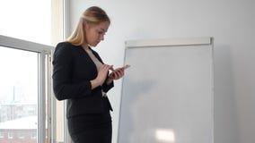 Bedrijfsvrouw die mobiele telefoon op flipchart in conferentieruimte met behulp van stock videobeelden