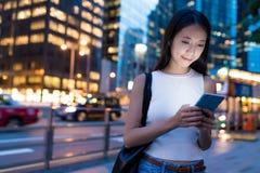 Bedrijfsvrouw die mobiele telefoon in stad bij nacht bekijken stock afbeelding