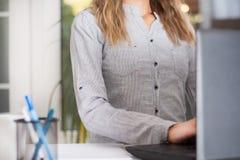 Bedrijfsvrouw die in modern bureau aan laptop werken stock afbeelding