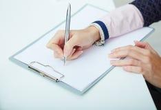 bedrijfsvrouw die nota's maken op het bureauwerk Stock Foto's