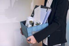 Bedrijfsvrouw die omhoog inpakkend al zijn persoonlijke bezittingen a dragen stock fotografie