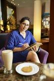 Bedrijfsvrouw die ontbijt in koffie hebben stock fotografie