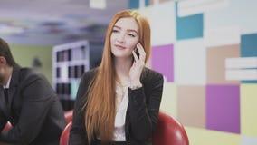 Bedrijfsvrouw die op de telefoon op het kantoor spreken stock video