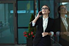 Bedrijfsvrouw die op slimme telefoon op bureauterras spreken Stock Foto's