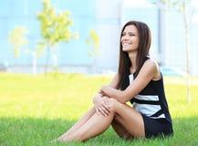 Bedrijfsvrouw die in openlucht op het gras zitten royalty-vrije stock foto