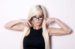 Bedrijfsvrouw die over haar glazen kijken Stock Foto's