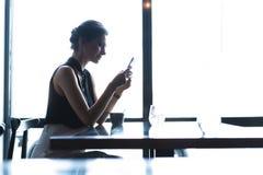 Bedrijfsvrouw die smartphone gebruiken tijdens lunch in koffie royalty-vrije stock afbeelding