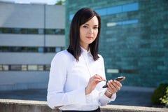 Bedrijfsvrouw die smartphone op de straat gebruiken stock afbeelding