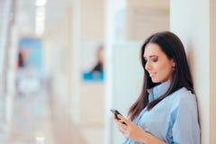 Bedrijfsvrouw die Telefoon in de Bureaubouw controleren royalty-vrije stock fotografie