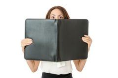 Bedrijfsvrouw die van achter een omslag kijken royalty-vrije stock afbeelding