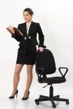 Bedrijfsvrouw die zich dichtbij bureaustoel bevinden Stock Foto's