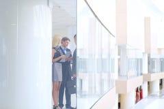 Bedrijfsvrouw die zich met haar personeel op achtergrond op modern kantoor bevinden stock fotografie