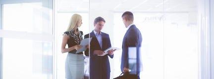 Bedrijfsvrouw die zich met haar personeel op achtergrond op modern kantoor bevinden royalty-vrije stock afbeelding